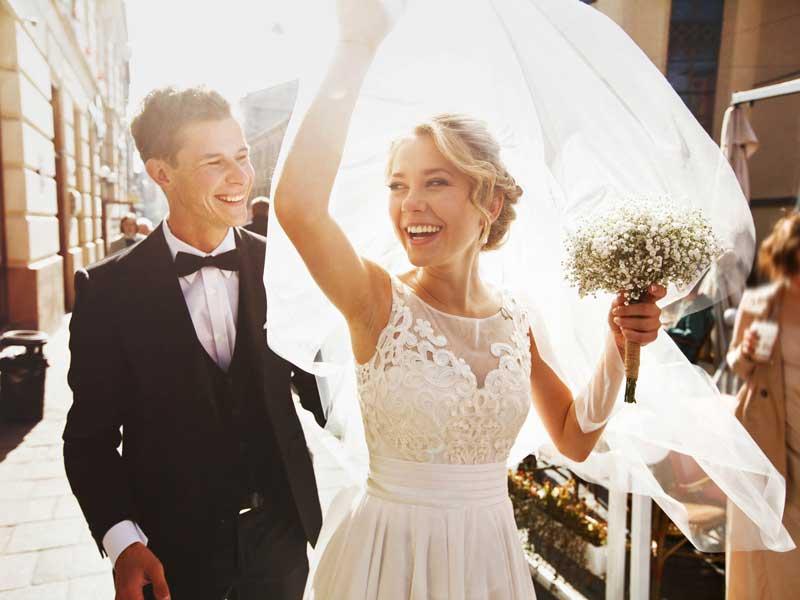 Bride and groom celebrating wedding in street